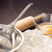 Baking ingredients with rolling-pin on board — Stock Photo