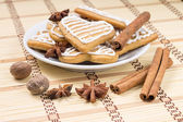 Christmas gingerbread cookies in plate with spices on bamboo background — Stock Photo