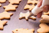 Decorating of gingerbread bears on wooden table — Stock Photo