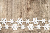 Christmas decoration. Plastic snowflakes on wood background — Stock Photo