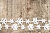 Kerstdecoratie. kunststof sneeuwvlokken op hout achtergrond — Stockfoto