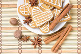Gingerbread cookies with spices on bamboo background — Stock Photo