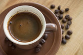 Cup of Coffee with beans on wood background — Stock Photo