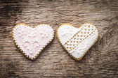 Two decorative heart cookies on textured wood background — Stock Photo