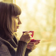Coffee. Pretty Girl drinking Coffee or Tea near Window. Warm colors toned — Stock Photo