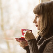 Beautiful girl drinking Coffee or Tea near Window — Stock Photo