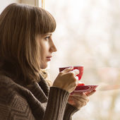 Young Pretty Woman Drinking Coffee or Tea near Window in Cafe — Stock Photo