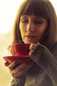 Young Beautiful Woman Drinking Coffee or Tea with Steam. Warm color toned — Stock Photo