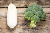 Broccoli and Cabbage on textured grunge wooden board. Top View — Stock Photo