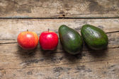 Two avocado and two apples on rural wooden background — Stock Photo