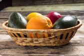 Various Fruits in Wicker on Greunge Wood Background — Stock Photo