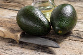 Two avocado with Knife and Bottle of Oil on Wood Background — Photo