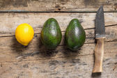 Avocado and Lemon with Knife on Old wooden Board — Stock Photo