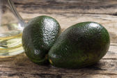 Two Raw Avocado with Bottle of Oil on Grunge Wood Background — Stock Photo