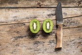 Cut in Half Kiwi with Knife lying on Textured Weathered Wooden T — Stock Photo
