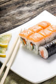 Seafood sushi rolls in white plate with chopsticks and japanese spices — Stock Photo