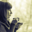 Beautiful girl drinking coffee or tea near window. Toned Image — Stock Photo