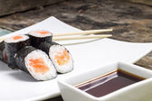 Makisushi on white plate. Seafood traditional maki sushi rolls with chopsticks — Foto de Stock