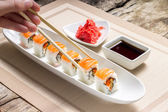 Eating with chopsticks seafood sushi rolls with traditional spices — Stock Photo