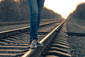 Girl walking across railroad. Warm color toned image — Stock Photo