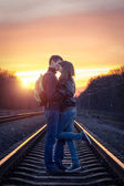 Romantic couple kissing at sunset on railroad — Stock Photo