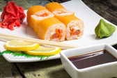 Traditional Philadelphia sushi rolls on white plate with chopstick and wasabi — Stock Photo