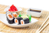 Seafood Maki-sushi rolls in plate with chopsticks on bamboo background — Stock Photo