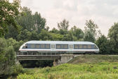 Speed train on railway at the country landscape — Stock Photo