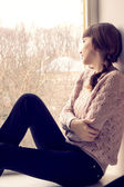Beautiful young woman sitting at the window.  Dreaming young gir — Stock Photo