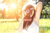 Young woman posing with old film camera in summer park — Stock Photo