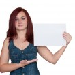 Happy woman showing blank signboard, isolated over white background — Stock Photo