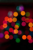 Christmas tree with defocused lights. Red background — Stock Photo