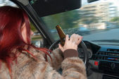 Drunk woman driving car with beer in hand — ストック写真