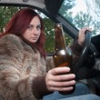 Drunk woman driving car with beer in hand — Stock Photo