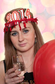 Smiling woman holding new year's champagne and balloons with color bokeh — Stock Photo