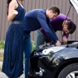 Stock Photo: Men helping women with broken car