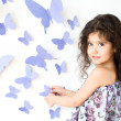 Stock Photo: Girl against wall decorated with butterfly