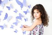 La ragazza contro una parete decorata con farfalla — Foto Stock