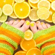Female legs between citrus fruits - Stock Photo