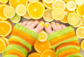 Female legs between citrus fruits — Stock Photo