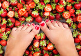 Female legs fresh summer berries — Stock Photo