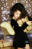 Curly girl in angel costume holding gift on her hands — Stock Photo