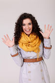 Portrait of young woman standing with hands up, isolated on grey — Stock Photo