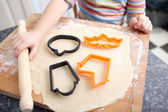 A little girl is making biscuits for halloween decoration in the — Stock Photo