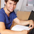 Young handsome guy with laptop and book, background - Foto de Stock