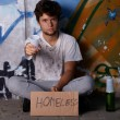 Homeless guy asking for help, sitting on a street - Stock Photo