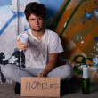 Stock Photo: Homeless guy asking for help, sitting on a street