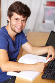Young handsome guy with laptop and book, background — Stock Photo