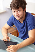 Young handsome guy with laptop and book, kitchen shoot — Stock Photo