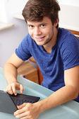 Jeune beau mec avec ordinateur portable et livre, cuisine shoot — Photo